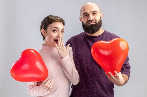 Jovem casal com roupas casuais, homem e mulher segurando balões em forma de coração, olhando para a câmera, feliz e surpreso, comemorando o dia dos namorados em pé sobre uma parede branca