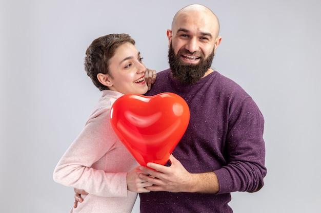Jovem casal com roupas casuais, homem e mulher segurando um balão em forma de coração, sorrindo alegremente feliz no amor, comemorando o dia dos namorados em pé sobre um fundo branco