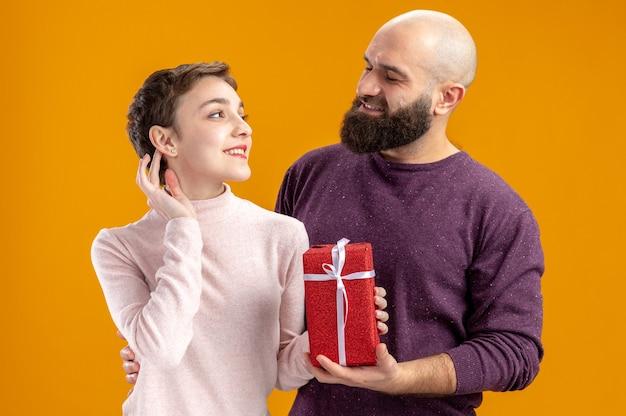 Jovem casal com roupas casuais mulher com cabelo curto com presente e um homem barbudo olhando um para o outro felizes no amor juntos comemorando o dia dos namorados em pé sobre a parede laranja