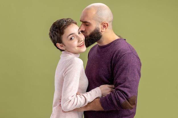 Jovem casal com roupas casuais mulher com cabelo curto e barbudo feliz apaixonada juntos homem beijando a namorada comemorando o dia dos namorados em pé sobre a parede verde