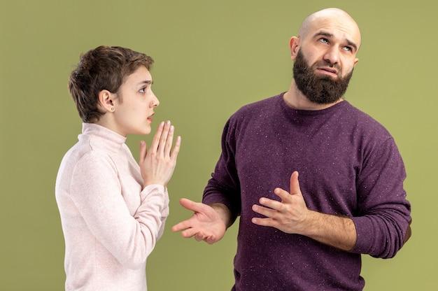 Jovem casal com roupas casuais mulher com cabelo curto pedindo perdão seu conceito de namorado barbudo confuso em pé sobre a parede verde