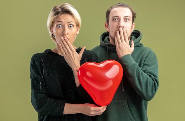 Jovem casal com roupas casuais, mulher e homem com balão em forma de coração olhando para a câmera espantado e surpreso, cobrindo a boca com as mãos, comemorando o dia dos namorados em pé sobre fundo verde