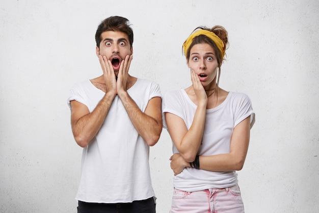 Jovem casal com roupas casuais olhando para a câmera