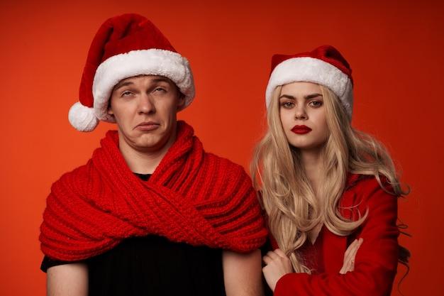 Jovem casal com roupas de ano novo, natal, feriado, fundo vermelho