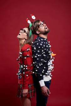 Jovem casal com roupas de natal estranhas amarradas com luzes de natal