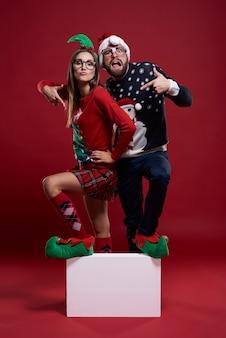Jovem casal com roupas estranhas de natal pisando em um cubo em branco