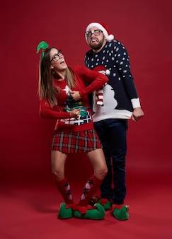 Jovem casal com roupas estranhas de natal