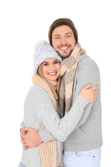 Jovem casal com roupas quentes em fundo branco. pronto para as férias de inverno