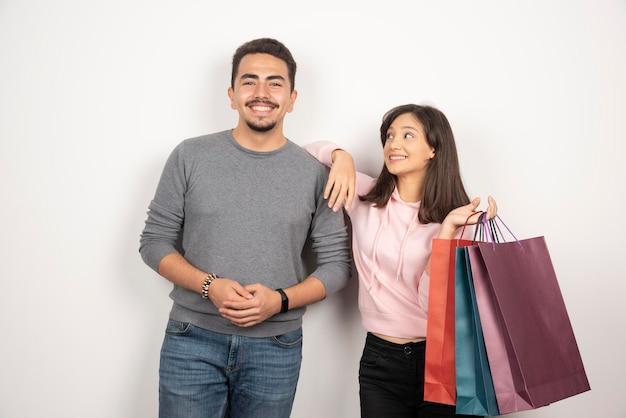 Jovem casal com sacolas de compras de pé em branco.