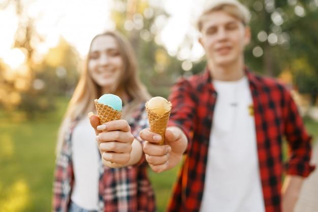 Jovem casal com sorvete caminhando no parque de verão.