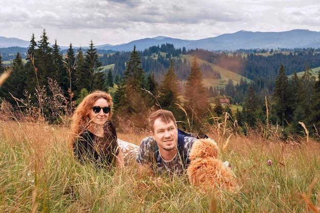 Jovem casal com um cachorrinho em uma caminhada em um fundo de montanhas