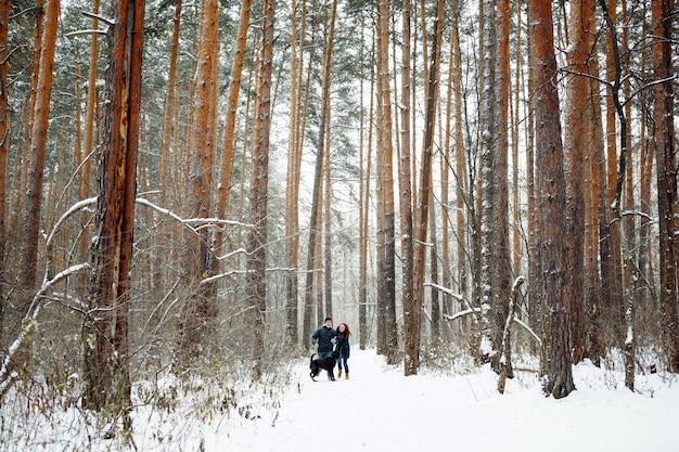 Jovem casal com um cachorro se divertindo no inverno