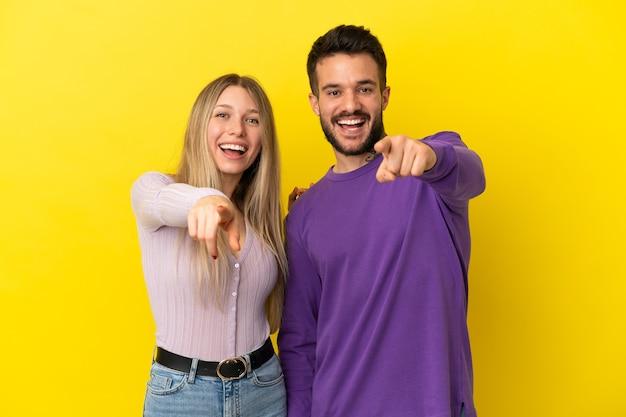 Jovem casal com um fundo amarelo isolado apontando o dedo para a frente