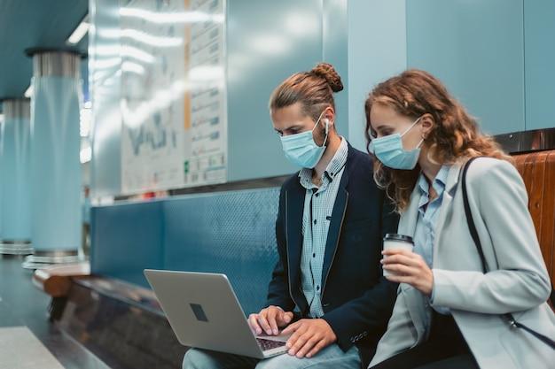 Jovem casal com um laptop na plataforma do metrô. foto com uma cópia-espaço.