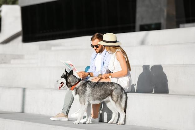 Jovem casal com um lindo cachorro husky ao ar livre