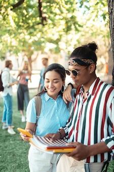 Jovem casal com um smartphone e livros nas mãos, juntos sob uma árvore no pátio da universidade