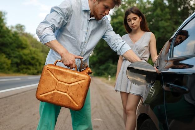 Jovem casal com uma lata de gasolina, sem gasolina, quebra do carro.