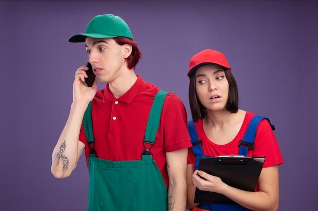 Jovem casal com uniforme de trabalhador da construção civil e boné concentrado cara falando no telefone olhando para baixo, garota curiosa, olhando para o lado, segurando a prancheta, ouvindo uma conversa ao telefone