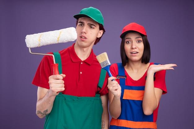 Jovem casal com uniforme de trabalhador da construção civil e boné confuso, segurando e olhando para o rolo de pintura, impressionada garota segurando o pincel, mostrando a mão vazia na parede roxa