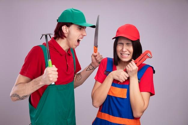 Jovem casal com uniforme de trabalhador da construção civil e boné menina assustada segurando a chave de cachimbo com os olhos fechados cara bravo segurando enxada e serra olhando para a menina gritando