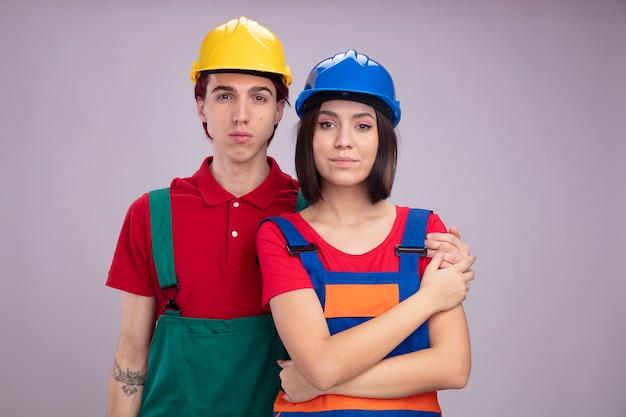 Jovem casal com uniforme de trabalhador da construção civil e cara sério de capacete de segurança em pé atrás de uma garota confiante, mantendo a mão em seu braço, garota tocando sua mão, ambos isolados