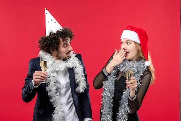 Jovem casal comemorando ano novo na mesa vermelha, feriado, amor, festa de natal