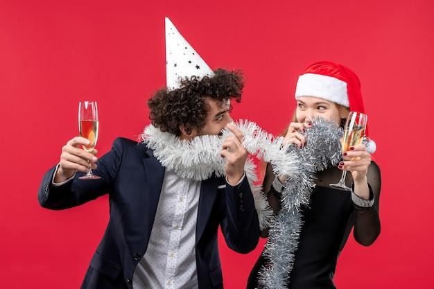 Jovem casal comemorando ano novo na mesa vermelha, feriado de amor de natal