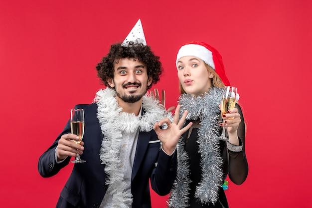 Jovem casal comemorando ano novo na parede vermelha, feriado, cor, natal