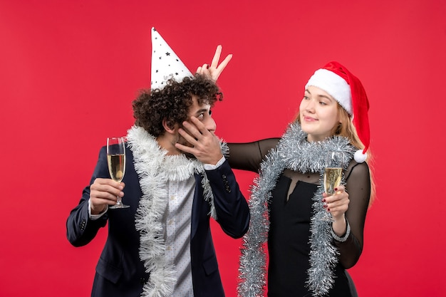 Jovem casal comemorando ano novo na parede vermelha