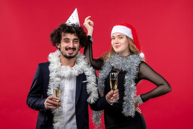Jovem casal comemorando ano novo no feriado de parede vermelha natal amor