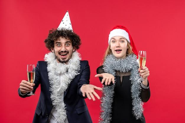 Jovem casal comemorando o ano novo na festa da mesa vermelha ama o natal