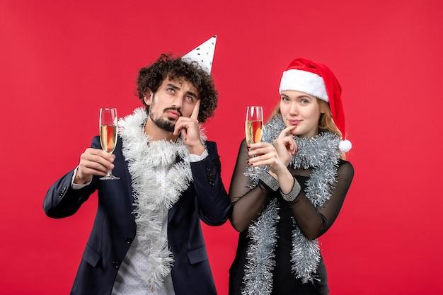 Jovem casal comemorando o ano novo na festa de amor de natal de parede vermelha