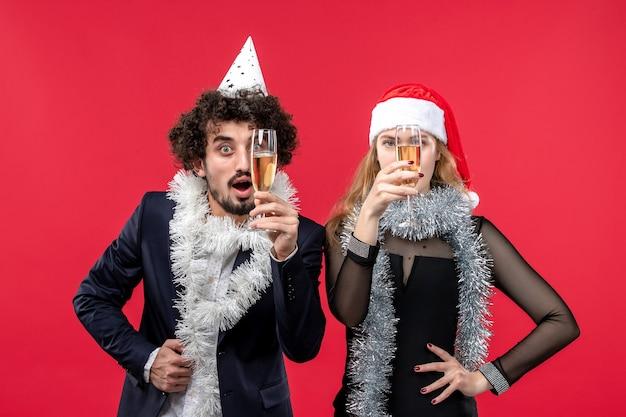 Jovem casal comemorando o ano novo na mesa vermelha, festa de amor de natal