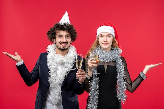 Jovem casal comemorando o ano novo na mesa vermelha. foto de amor de natal