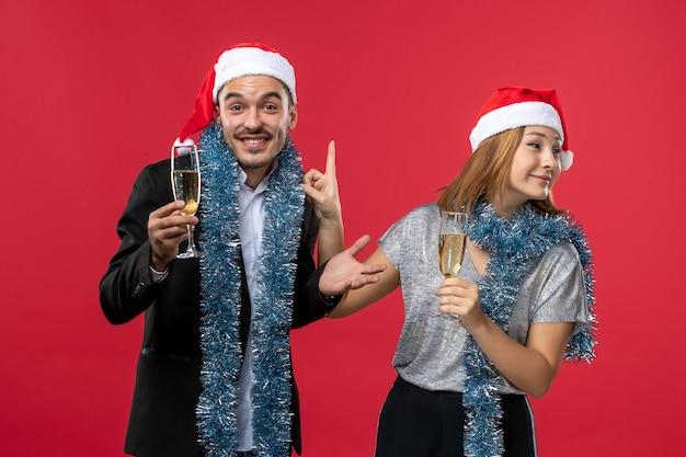 Jovem casal comemorando o ano novo na parede vermelha