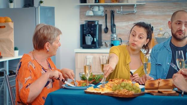 Jovem casal comemorando o dia de ação de graças com parentes. multi geração, quatro pessoas, dois casais felizes conversando e comendo durante um jantar gourmet, curtindo o tempo em casa.