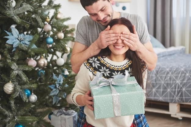 Jovem casal comemorando o natal. um homem de repente apresentou um presente para sua esposa. o conceito de felicidade e bem-estar da família