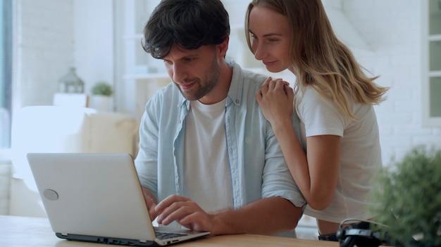Jovem casal comemorando o sucesso, lendo boas notícias no e-mail, olhando para a tela do laptop, na cozinha de casa
