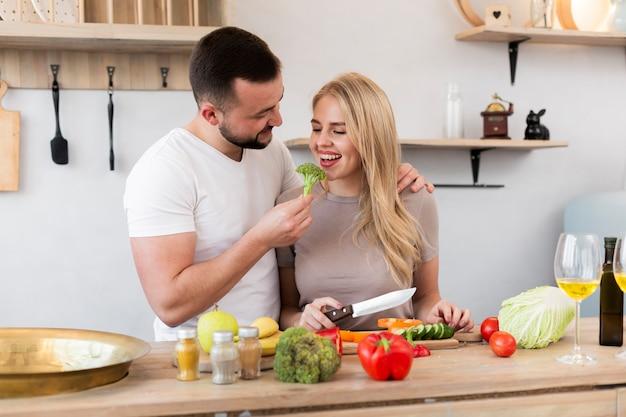 Jovem casal comendo brócolis