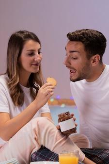 Jovem casal comendo doces na cama