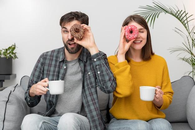 Jovem casal comendo donuts
