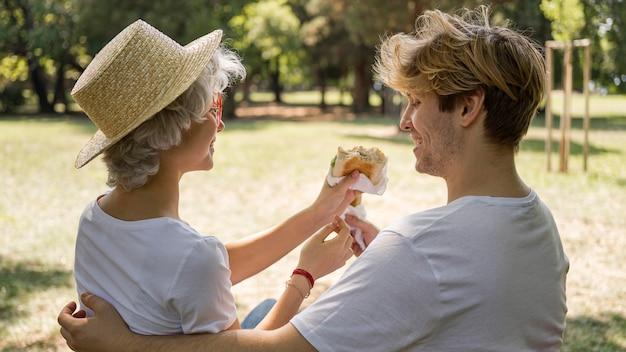 Jovem casal comendo hambúrgueres juntos no parque