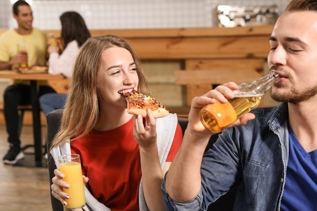 Jovem casal comendo pizza deliciosa em um café