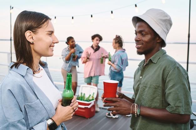 Jovem casal contemporâneo com bebidas olhando um para o outro com sorrisos