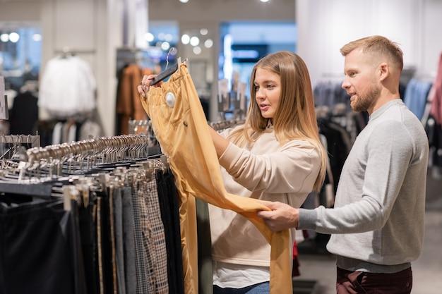 Jovem casal contemporâneo olhando para calças amarelas no cabide no departamento de roupas enquanto escolhe novas roupas casuais à venda