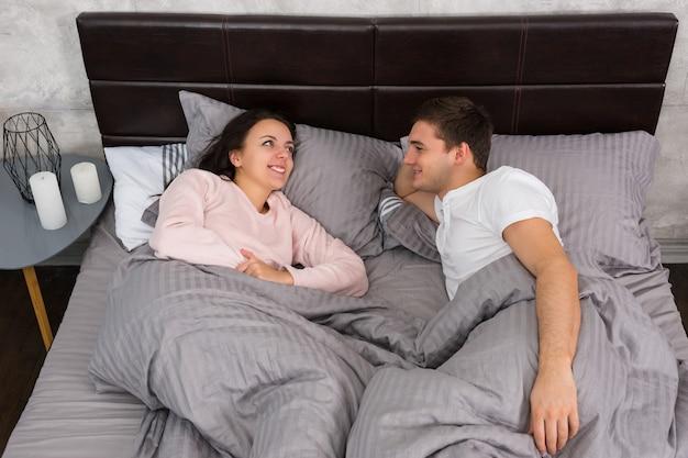Jovem casal conversando deitado na cama e de pijama perto da mesa de cabeceira com velas no quarto em estilo loft com cores cinza