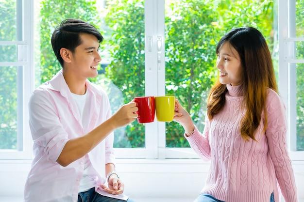 Jovem casal conversando e bebe bebida em casa