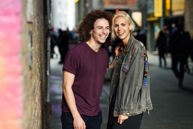 Jovem casal conversando no meio urbano, numa rua típica de londres.