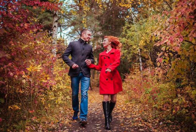 Jovem casal corre na floresta de outono entre árvores coloridas