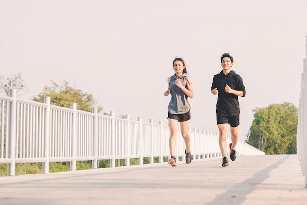 Jovem casal corredor correndo na estrada em execução no parque da cidade